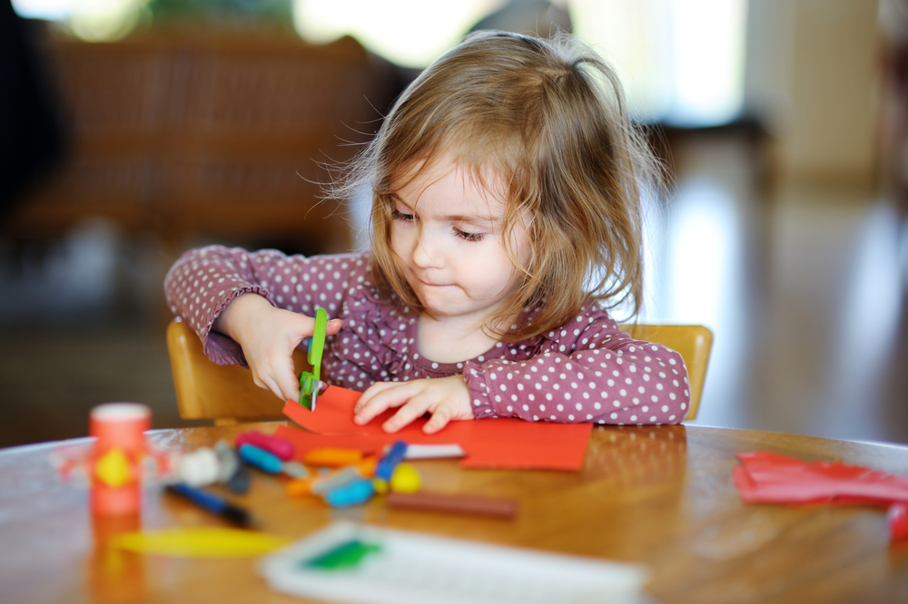 Preschool Girl cutting colorful paper