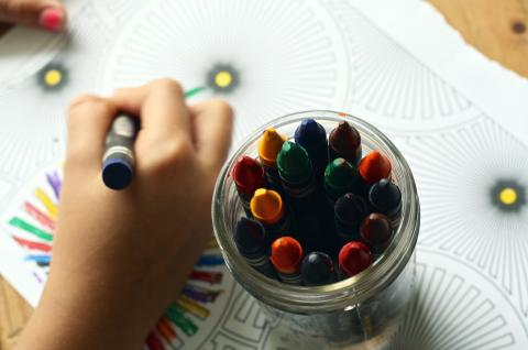 Crayons and a child coloring
